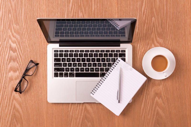 Bloco de notas vazio sobre o copo do portátil e de café na tabela de madeira imagem de stock royalty free