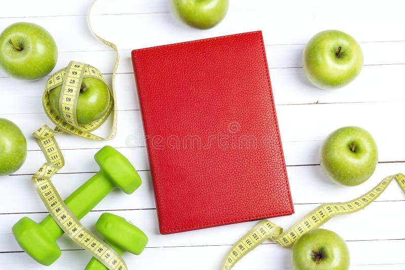 Bloco de notas vermelho com pesos verdes e maçãs com fita de medição foto de stock