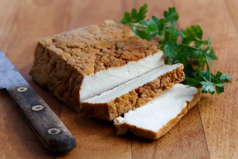 Bloco de tofu fumado, de duas fatias do tofu, de faca rústica e de p fresco fotografia de stock