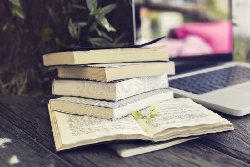 Bloco dos livros com o portátil na tabela de madeira imagem de stock