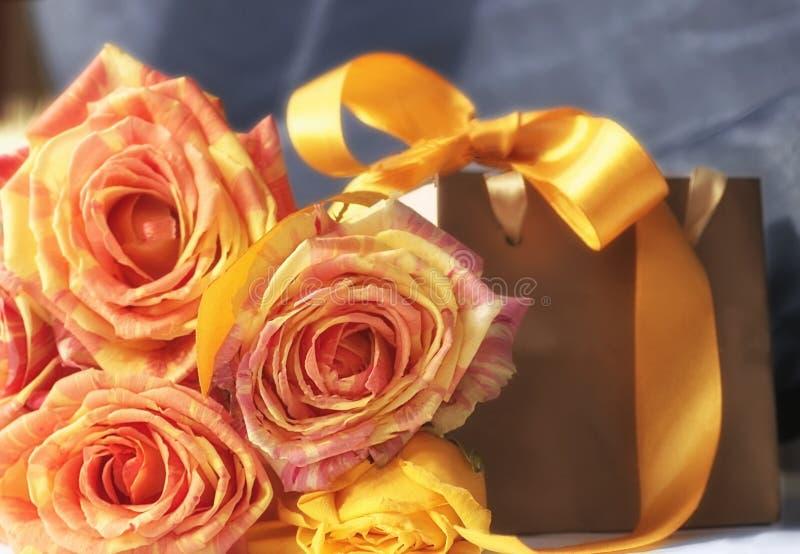 Bloco dourado do presente, flores cor-de-rosa da laranja e fita decorativa amarela fotografia de stock royalty free