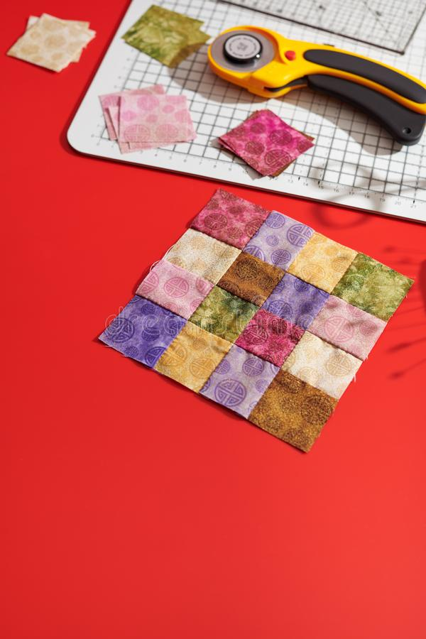 Bloco estofando das partes quadradas brilhantes de telas, cortador giratório, régua, esteira do ofício, partes quadradas de telas fotografia de stock royalty free