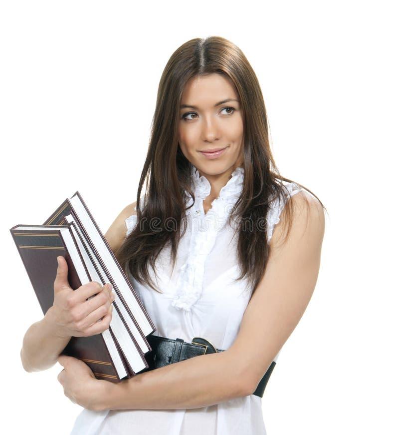 Bloco moreno da posse do estudante de mulher da atribuição do estudo dos trabalhos de casa dos livros fotografia de stock