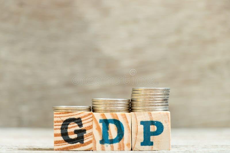 Bloco na palavra GDP ( Product) doméstico bruto; com a moeda na tendência do aumento no fundo de madeira imagem de stock royalty free