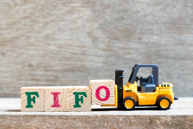 Bloco o da letra da posse da empilhadeira do brinquedo para terminar a abreviatura da palavra FIFO de primeiramente - em/primeira fotografia de stock royalty free