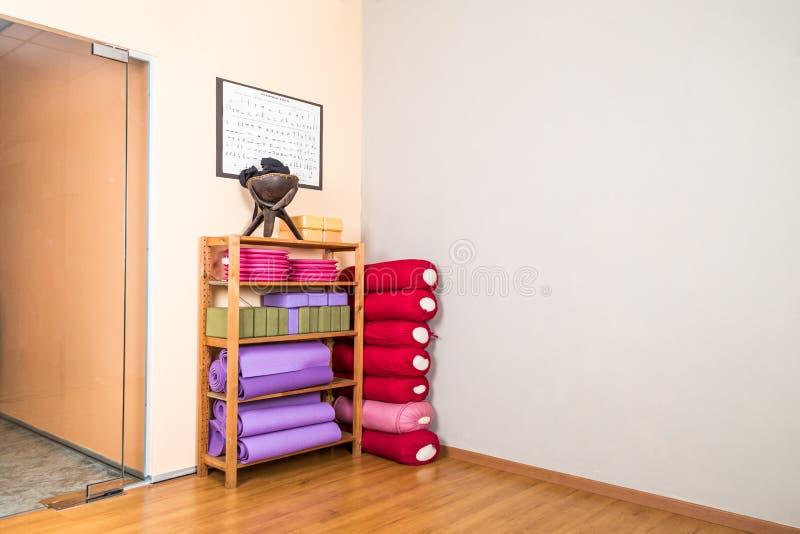 Blocos da ioga, descanso, esteiras, almofadas, acessórios empilhados no stu da ioga fotos de stock royalty free