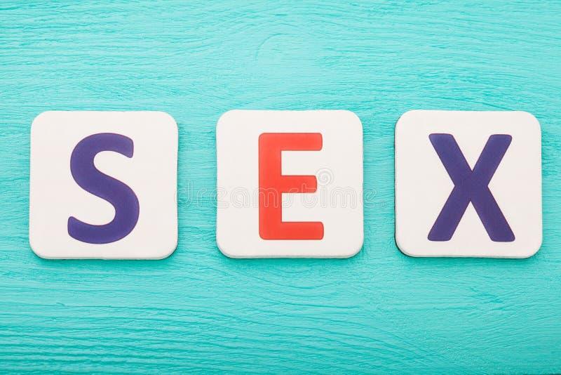 Blocos da palavra do sexo por carta no fundo de madeira azul Vista superior Copie o espaço fotografia de stock royalty free