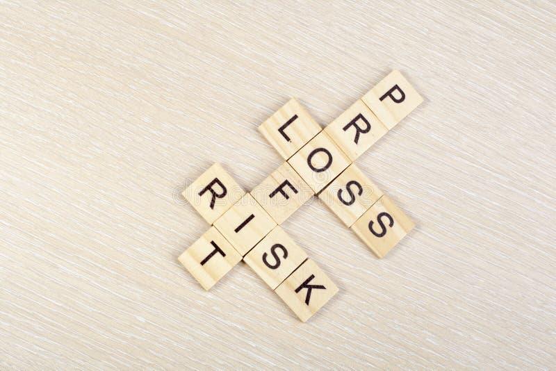 Blocos das palavras cruzadas do lucro, da perda e do risco na tabela Vista superior imagens de stock