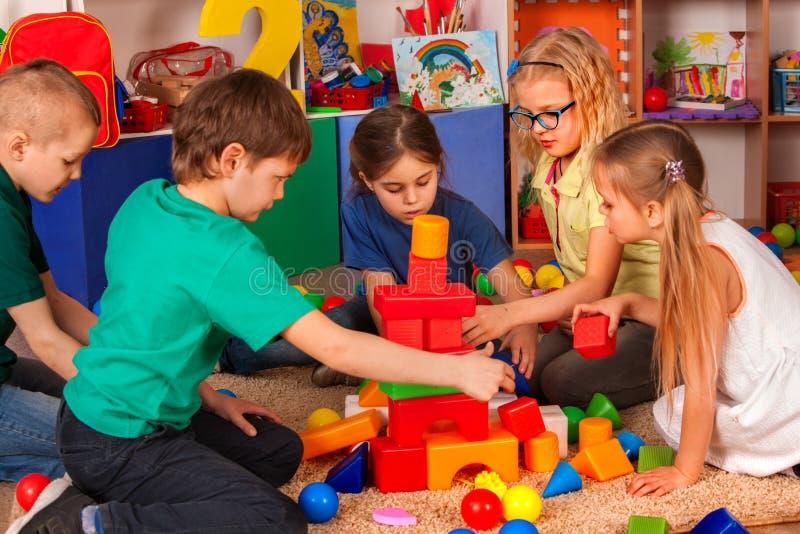 Blocos de apartamentos das crianças no jardim de infância Crianças do grupo que jogam o assoalho do brinquedo imagens de stock royalty free