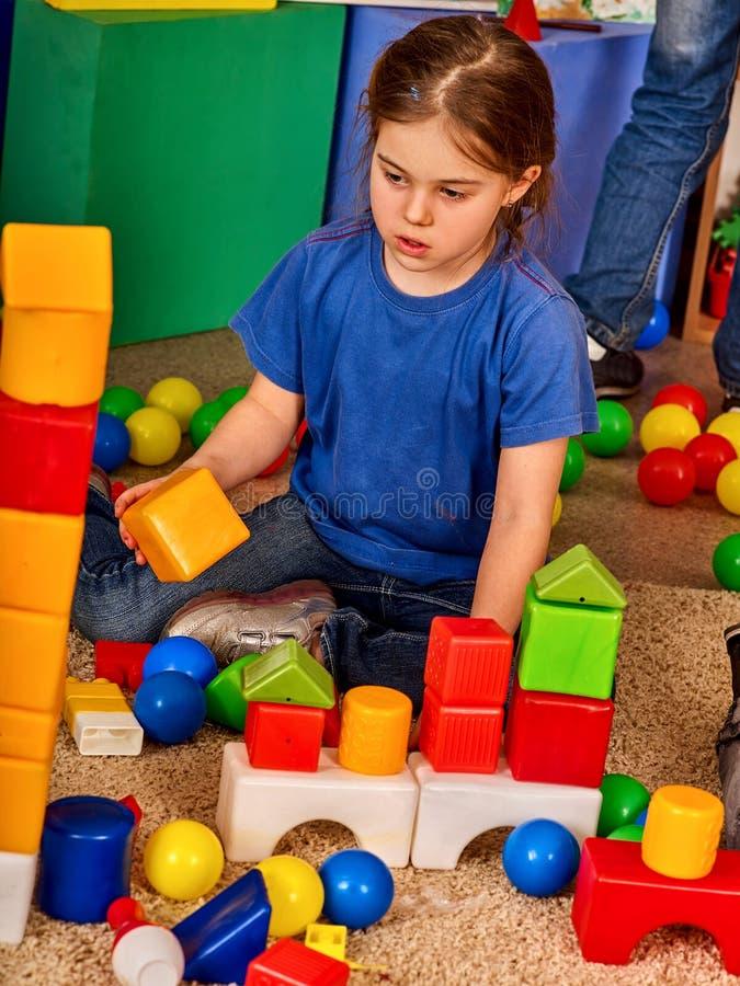 Blocos de apartamentos das crianças no jardim de infância Crianças do grupo que jogam o assoalho do brinquedo imagem de stock royalty free