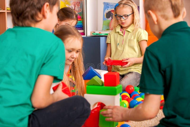 Blocos de apartamentos das crianças no jardim de infância Crianças do grupo que jogam o assoalho do brinquedo fotos de stock