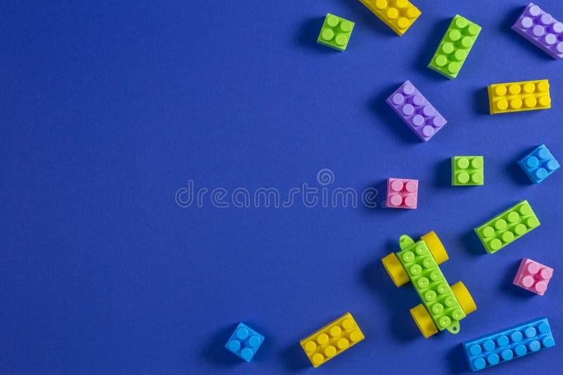 Blocos de apartamentos plásticos coloridos do carro do brinquedo no fundo azul imagens de stock royalty free
