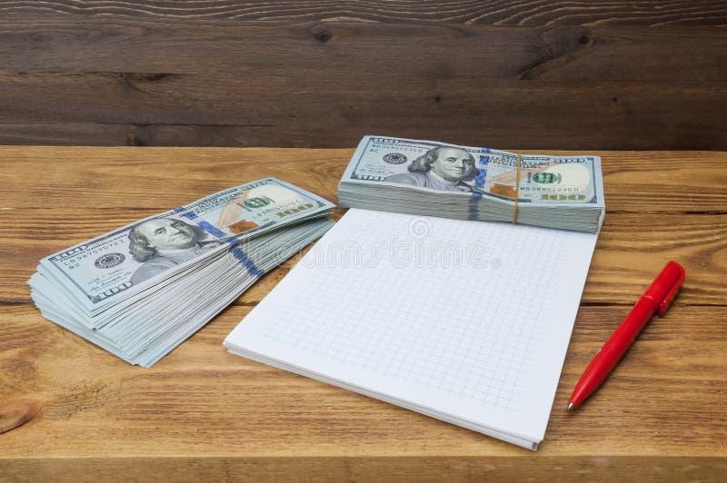 Blocos de cem dólares, de um caderno e de uma mentira da pena em uma tabela de madeira textured imagens de stock royalty free