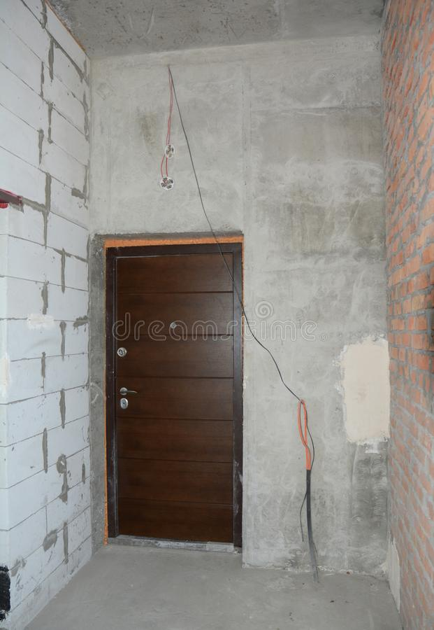 Blocos de cimento ventilados e parede incompleta da casa do tijolo com reparo, a instalação da porta do metal do renovatin imagem de stock royalty free