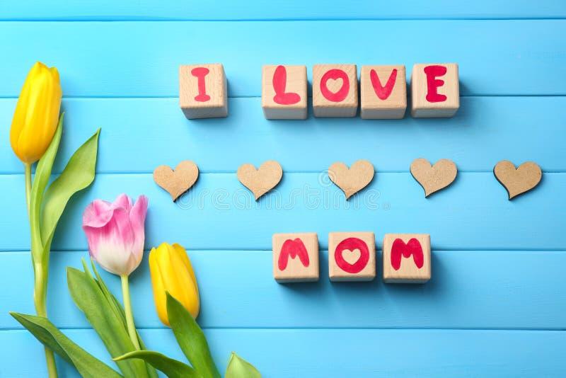Blocos de madeira com as letras que formam a frase EU AMO A MAMÃ e flores bonitas no fundo da cor imagens de stock royalty free