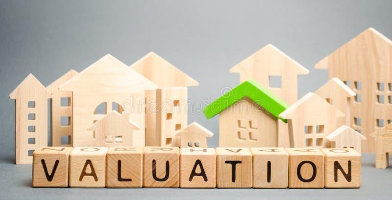 Blocos de madeira com a avaliação da palavra e muitas casas Condi??o residencial da propriedade da revenda O estudo do estado da  imagens de stock