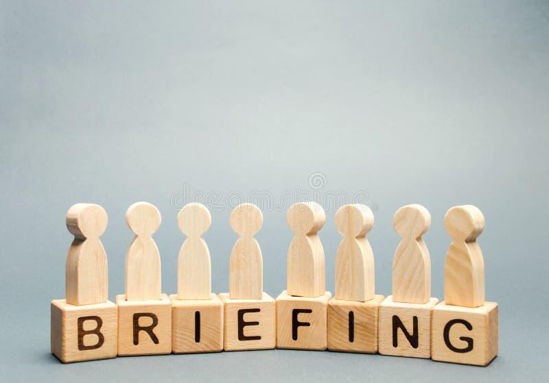 Blocos de madeira com a instrução da palavra e uma multidão de empregados Conferência de imprensa curto informativa reunião coope imagem de stock royalty free