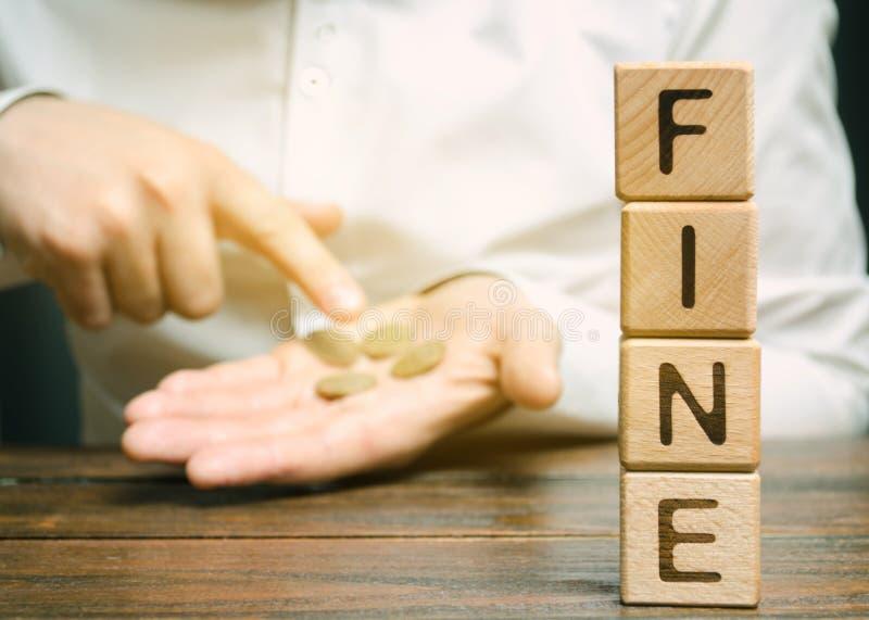 Blocos de madeira com a multa da palavra e um homem que calcule o tamanho da multa Pena monetária imposta sob a forma da punição fotografia de stock royalty free