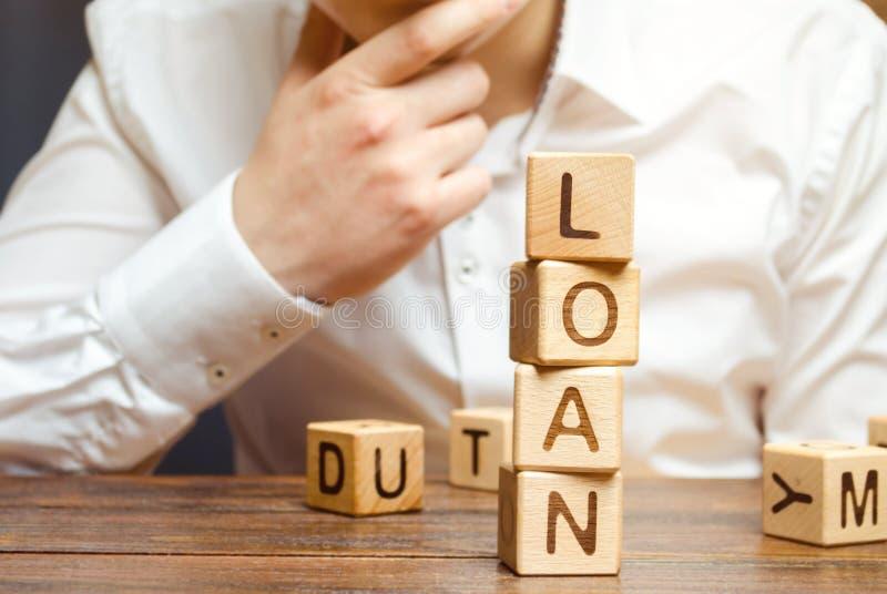 Blocos de madeira com o empréstimo e o homem de negócios da palavra Empréstimo do consumidor, da operação bancária e da proprieda foto de stock