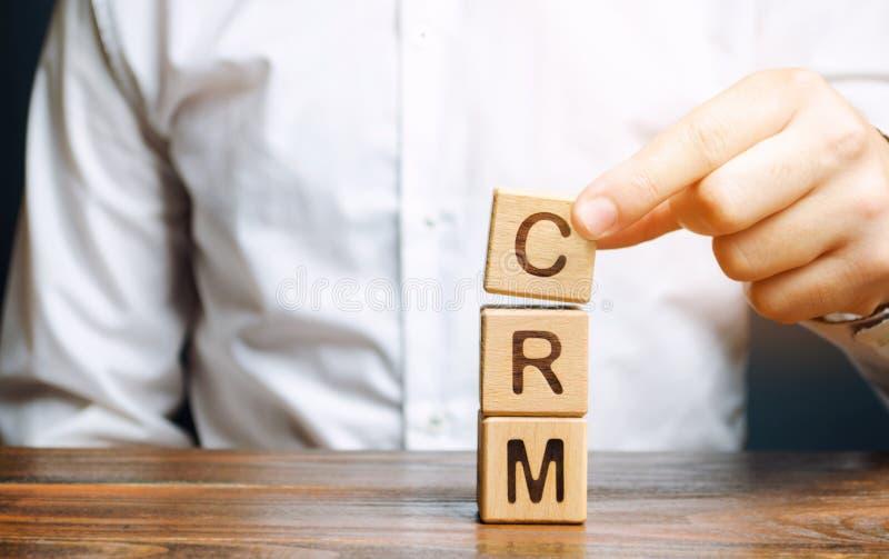 Blocos de madeira com o gerenciamento de relacionamento com o cliente e o homem de negócios da palavra CRM Estratégias da automat foto de stock