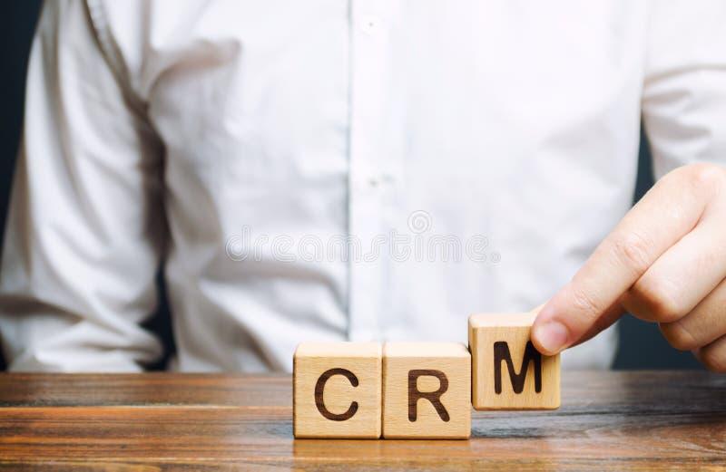 Blocos de madeira com o gerenciamento de relacionamento com o cliente e o homem de negócios da palavra CRM Estratégias da automat fotografia de stock