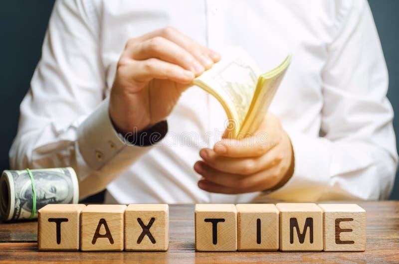 Blocos de madeira com o tempo do imposto da palavra e contribuinte com um dinheiro Impostos anuais da propriedade/renda O conceit imagem de stock