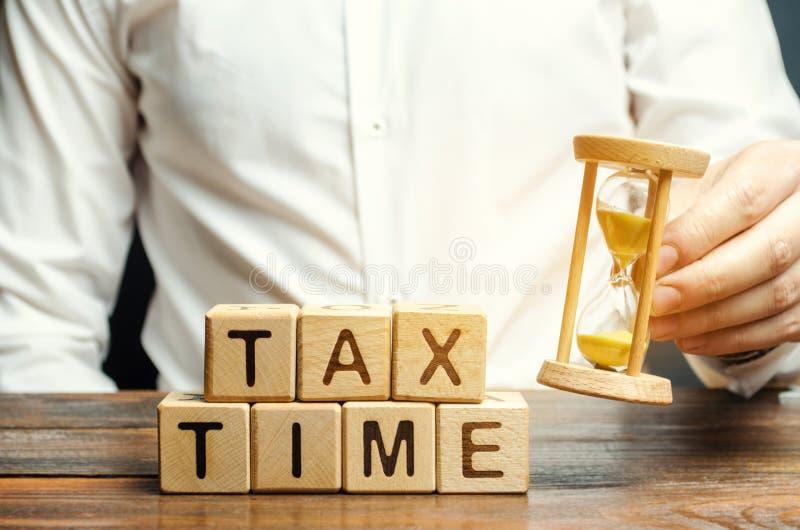 Blocos de madeira com o tempo do imposto da palavra e contribuinte com uma ampulheta O conceito de pagar a taxa de imposto Tribut imagens de stock royalty free