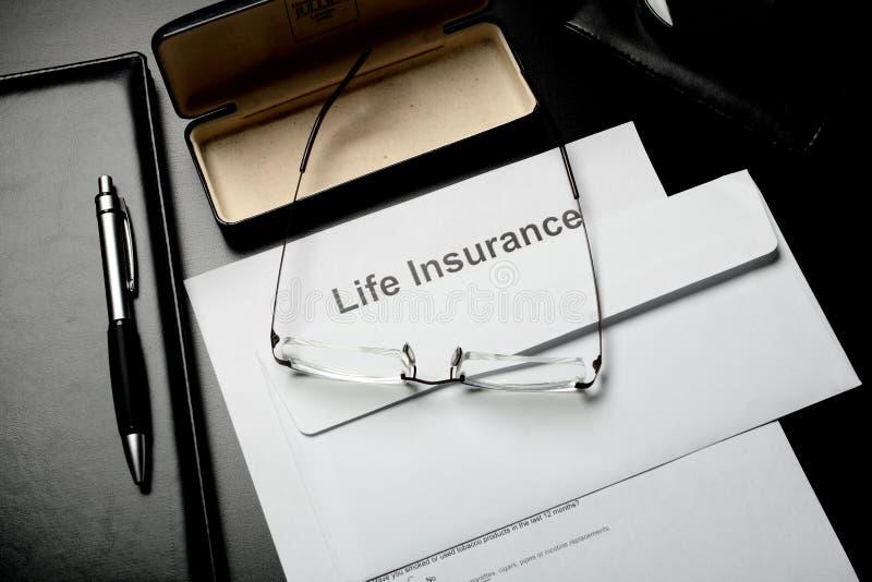 Blocos de notas, vidros e papéis do seguro de vida foto de stock royalty free