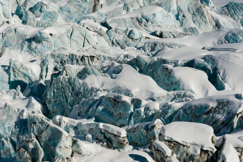 Blocos e fissuras de gelo do fluxo da geleira cobertos de neve no inverno fotografia de stock