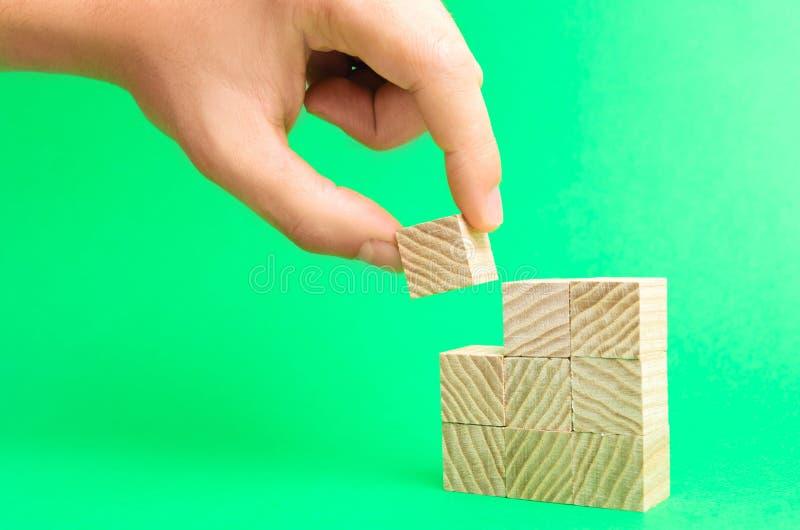 Blocos e mão de madeira do ` s do homem de negócios Conceito da construção dos bens imobiliários A mão do ` s do arquiteto guarda fotografia de stock royalty free