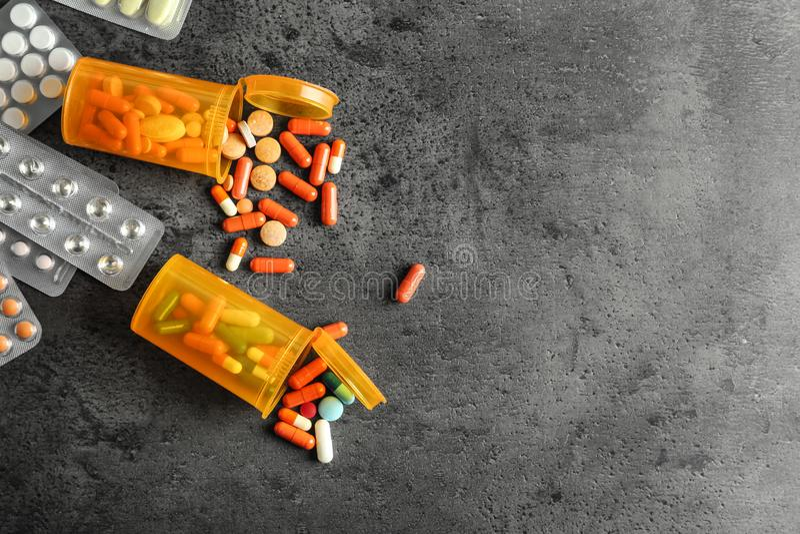 Blocos e recipientes de bolha com os comprimidos no fundo cinzento fotografia de stock