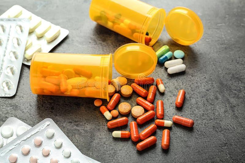 Blocos e recipientes de bolha com os comprimidos no fundo cinzento foto de stock