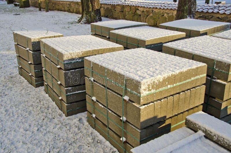 Blocs de béton de matériaux de construction dans la rue urbaine d'hiver photographie stock libre de droits