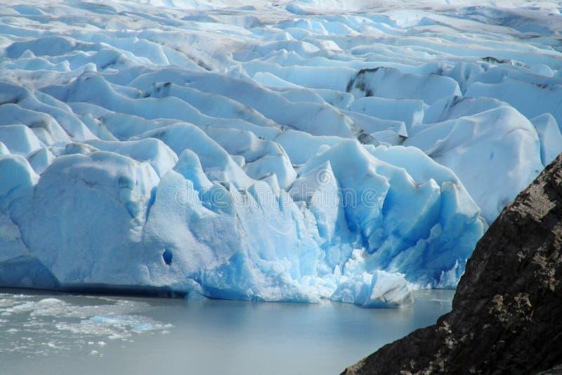 Blocs de glace bleus profonds du grand glacier de montagne images libres de droits