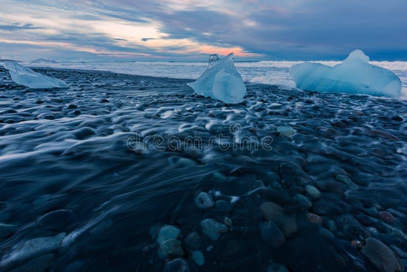 Blocs de glace sur la plage noire de sable pendant le coucher du soleil en Islande images stock