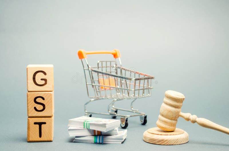 Blocs en bois avec le mot GST, l'argent et un chariot à supermarché avec le marteau d'un juge Impôt, qui est imposé à la vente de image stock