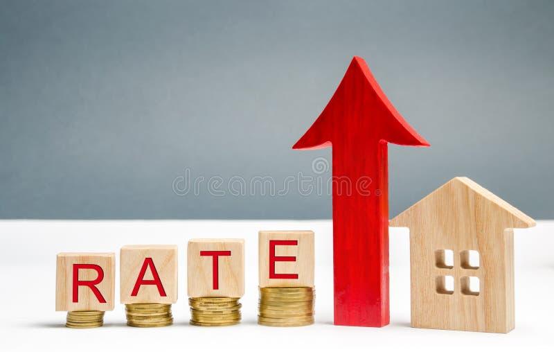 Blocs en bois avec le taux de mot, vers le haut de la flèche et de la maison en bois Le concept de soulever des taux d'intérêt su photo stock