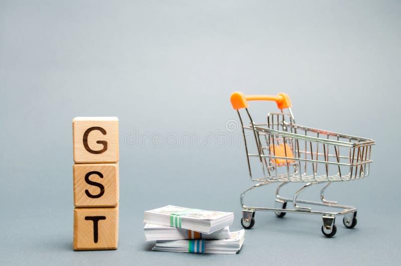 Blocs en bois avec les marchandises du mot GST et l'impôt de services, l'argent et un chariot à supermarché Impôt, dont est impos photos libres de droits
