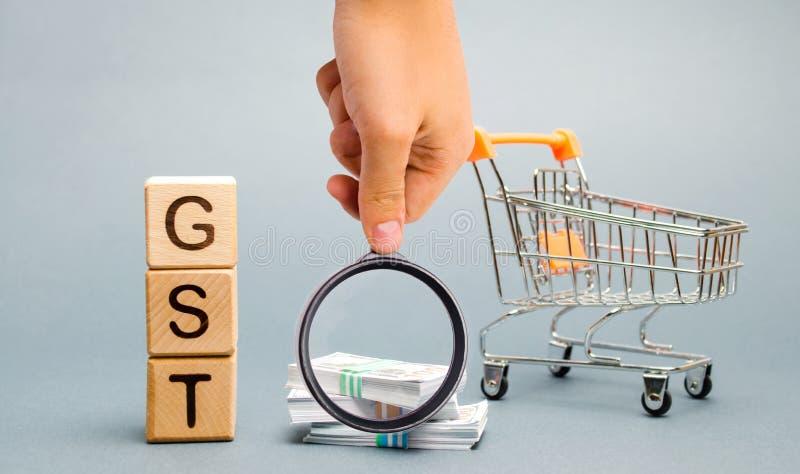 Blocs en bois avec les marchandises du mot GST et l'imp?t de services, l'argent et un chariot ? supermarch? Imp?t, dont est impos photo stock