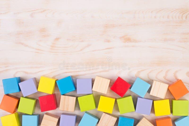 Blocs en bois colorés sur le fond en bois, vue supérieure avec l'espace de copie photo libre de droits