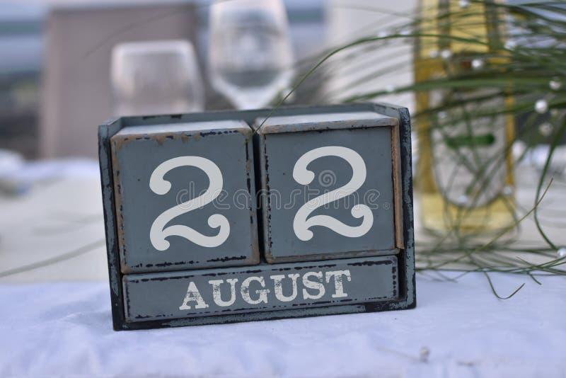 Blocs en bois dans la boîte avec la date, le jour et le mois 22 août images stock