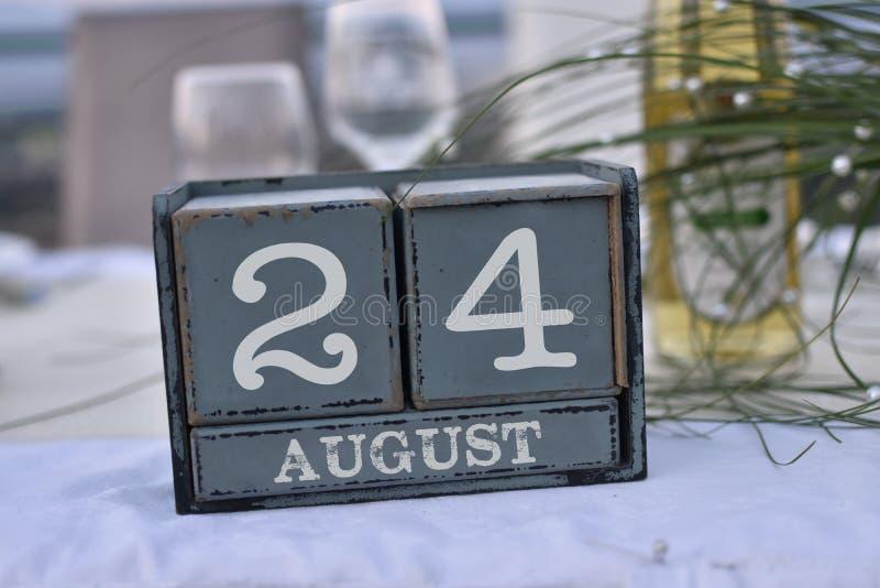 Blocs en bois dans la boîte avec la date, le jour et le mois 24 août images stock