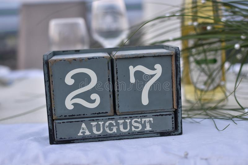 Blocs en bois dans la boîte avec la date, le jour et le mois 27 août photographie stock