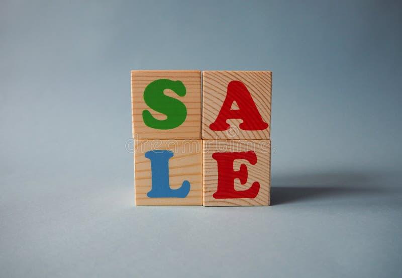 Blocs en bois de jouet d'alphabet avec le texte : vente Cubes multicolores d'isolement en ABC d'enfants sur le fond bleu image stock