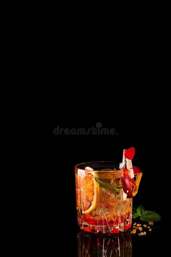 Blodapelsinmargaritacoctail med is och mintkaramellen på svart royaltyfri foto