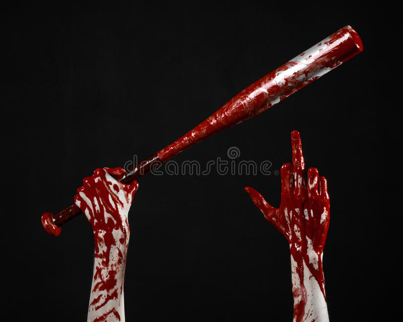Blodig hand som rymmer ett baseballslagträ, ett blodigt baseballslagträ, slagträ, blodsport, mördare, levande död, halloween tema royaltyfria bilder