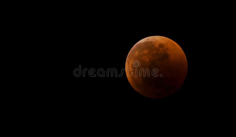 Blodig månenärbild mot en svart himmel som ett resultat av en astronomisk händelsemånförmörkelse Sikt i teleskop, placering på se arkivbild