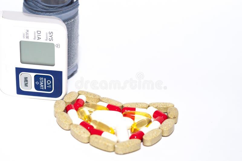 Bloeddrukcontroleur en kleurrijke die tabletten in hartvorm wordt geschikt royalty-vrije stock afbeelding
