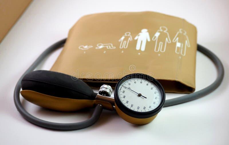 Bloeddrukmeter, of sphygmometer, met de band waarin zij de instructies voor gebruik worden gestempeld stock afbeelding
