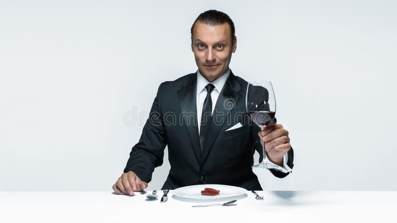 Bloedig Halloween-thema: gekke mens met een mes, een vork en een vlees stock fotografie